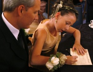 Ken Lane watches his daughter Hannah sign the purity covenant at the annual Father-Daughter Purity Ball in Colorado Springs